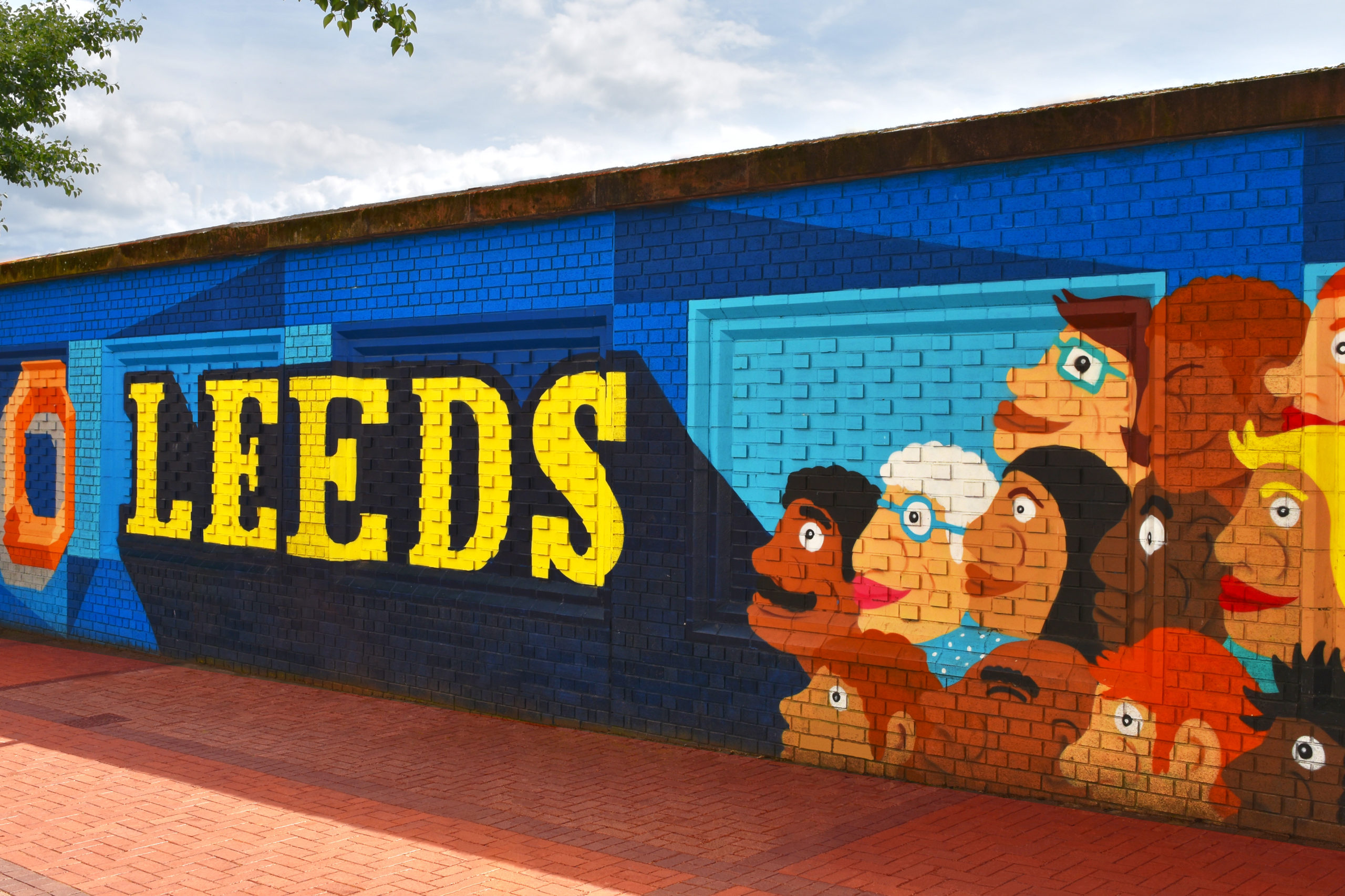 Mural, Leeds in yellow on blue background with faces